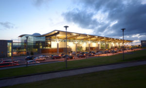 Cork airport terminal from the outside at dusk with the sun setting in the background