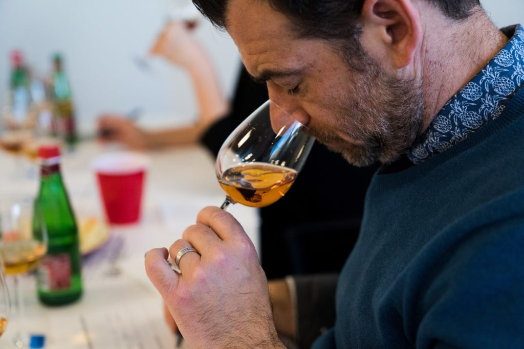 A man at a whiskey tasting event sniffs a glass of whiskey while wearing a blue jumper and check blue shirt underneath