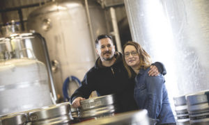 Sam and Maud Black of Black's Distillery, smilingwith their arms around each other in their distillery with steel vats in the background