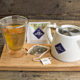 A display of herbal tea, a teapot and a glass cup of herbal tea.