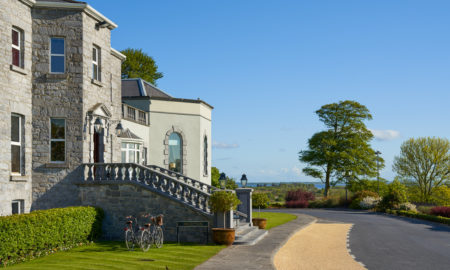 An outside picture of the Glenlo Abbey Hotel, Galway, on a sunny morning with clear skies