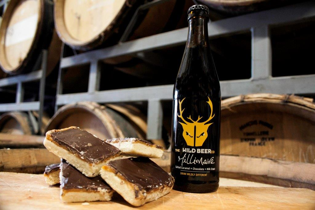 A bottle of Wild Beer brewery's Millionaire Chocolate Stout beside three chocolate caramel squares
